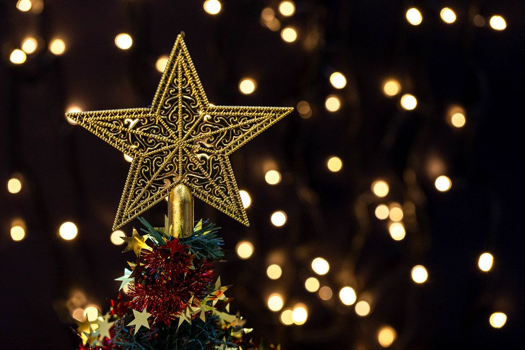 Golden star on top of a decorated Christmas tree on bokeh background (Flip 2019)