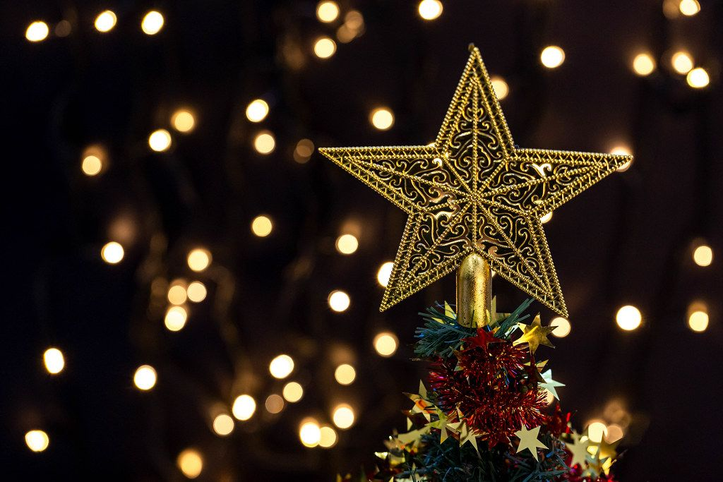 Golden star on top of a decorated Christmas tree on bokeh background