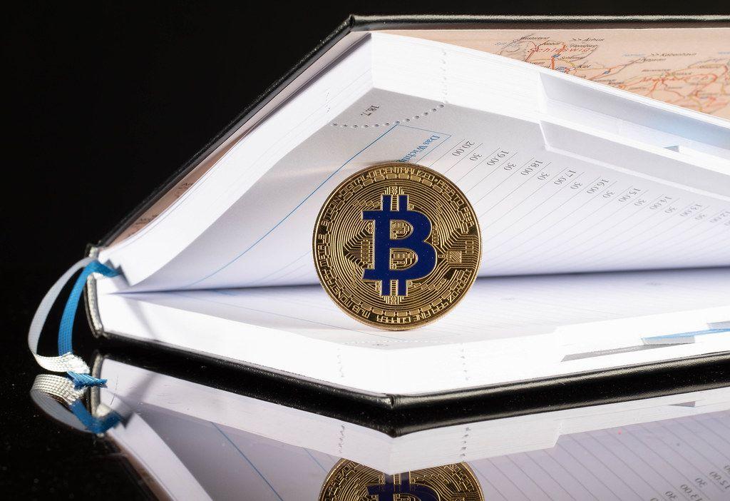 Goldene Bitcoin-Münze in einem offenen Notizbuch vor schwarzem Hintergrund