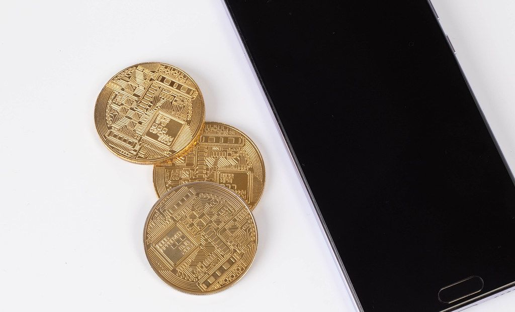 Goldene Geldmünzen neben dem Smartphone auf weißem Hintergrund