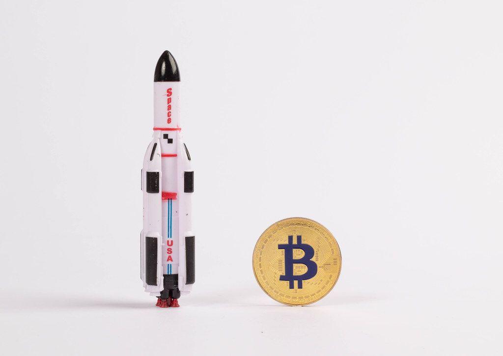 Goldener Bitcoin mit einem Raketenschiff