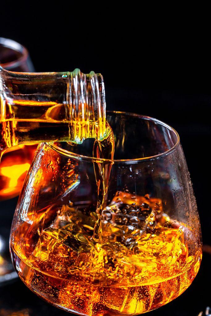 Goldener Cognac wird in mit Glas mit Eiswürfeln eingegossen