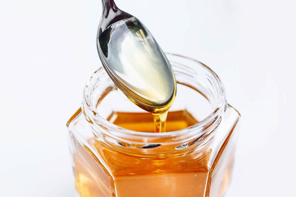 Goldfarbener Honig fließt einen Löffel hinab