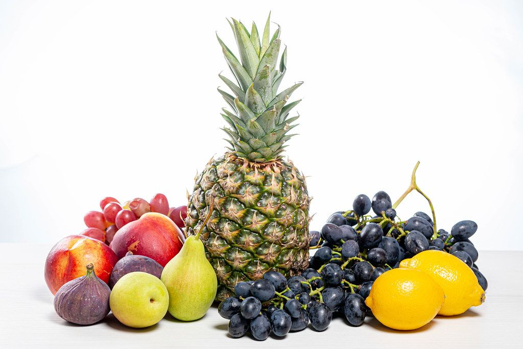 Grapes, pineapple, pears, apples, nectarine, figs and lemons on white background