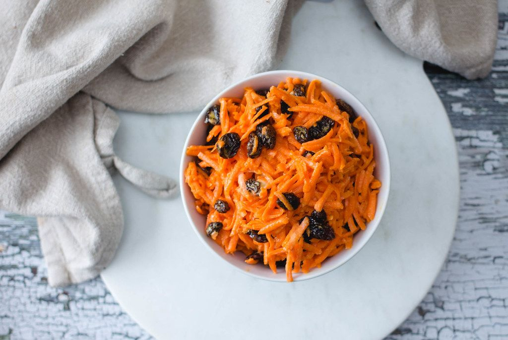 Grated Carrot Salad with Raisin in a White bowl
