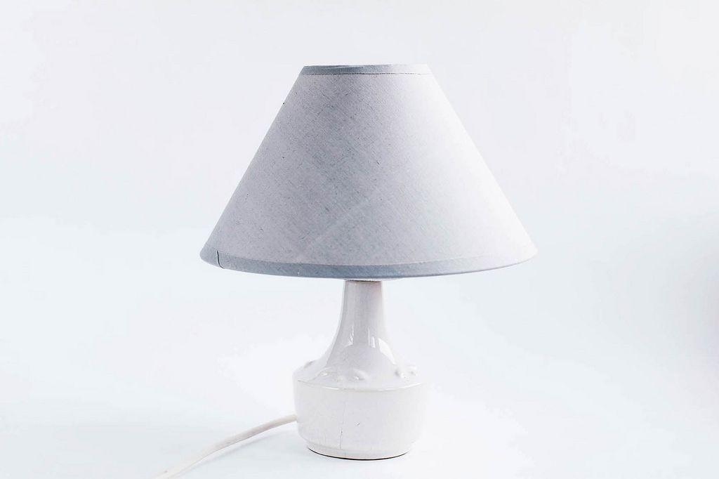 Graue Nachttischlampe vor weißem Hintergrund