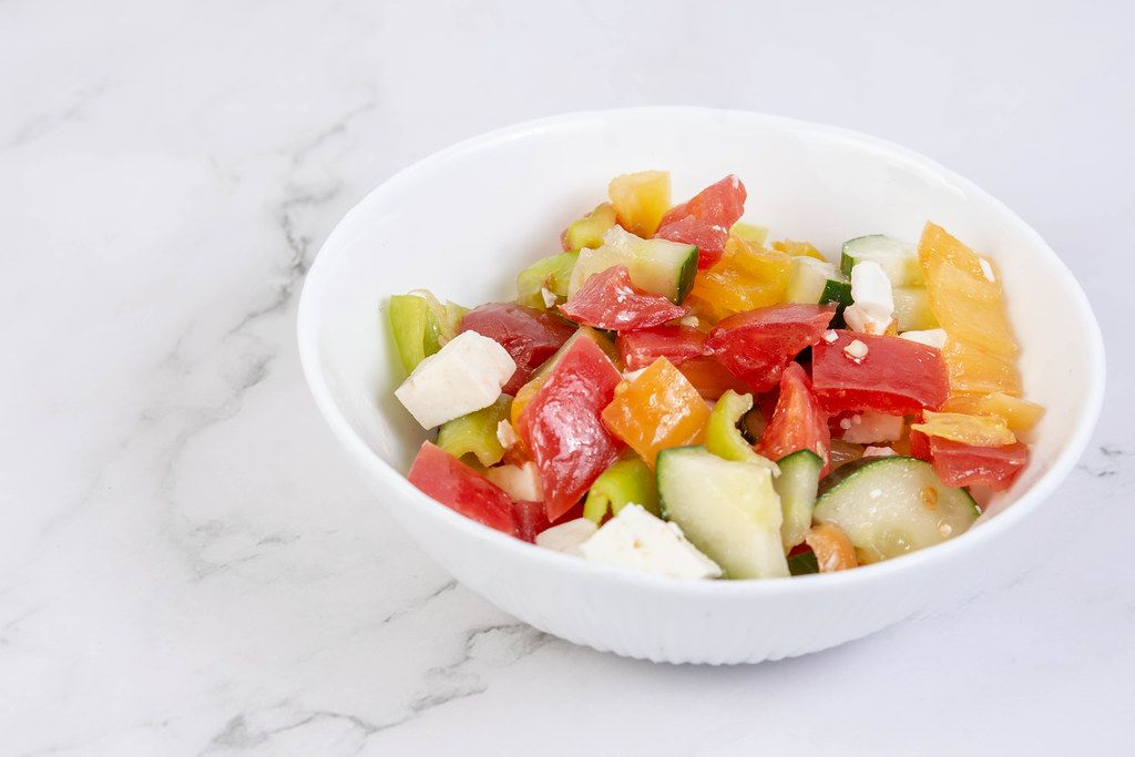 Greek Salad in the bowl above grey marble table