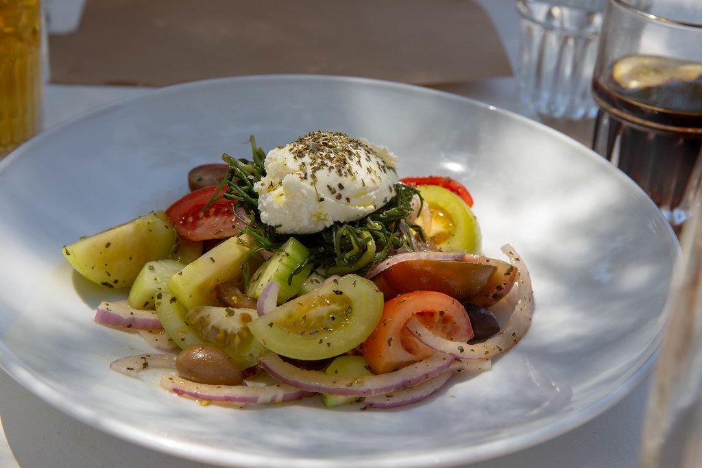 Greek salad with green tomatoes, onions and olives on a white plate in a Restaurant in Greece