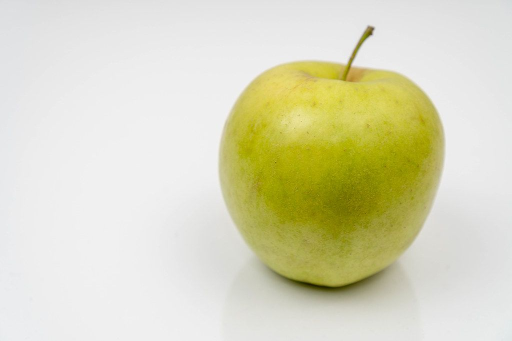 Green Apple on the white reflective surface with copy space