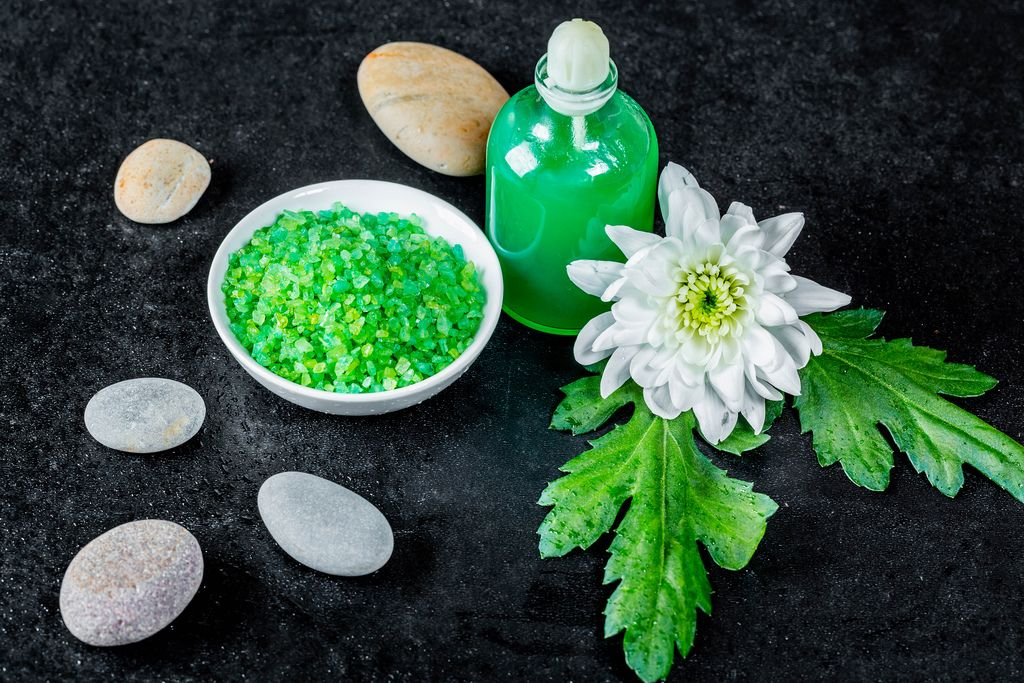Green salt and gel for Spa treatments with sea stones on a black background