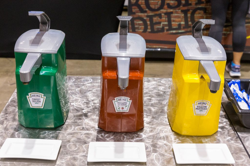 Green sweet relish, red tomato ketchup and yellow mustard in Heinz dispenser