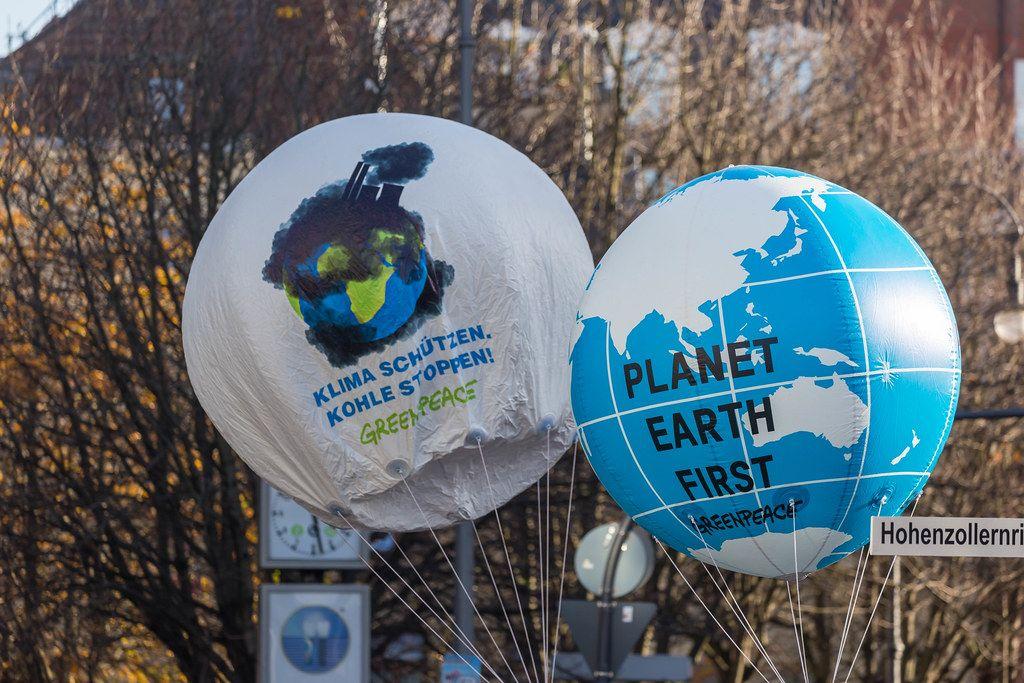 Greenpeace mit zwei Luftballons als Erdkugel