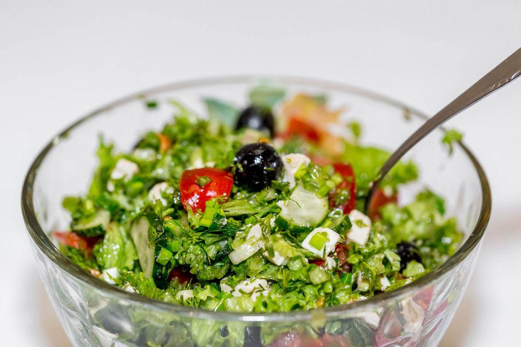 Griechischer Salat mit Oliven, Tomaten, Fetakäse und Kräutern in Glasschale vor weißem Hintergrund