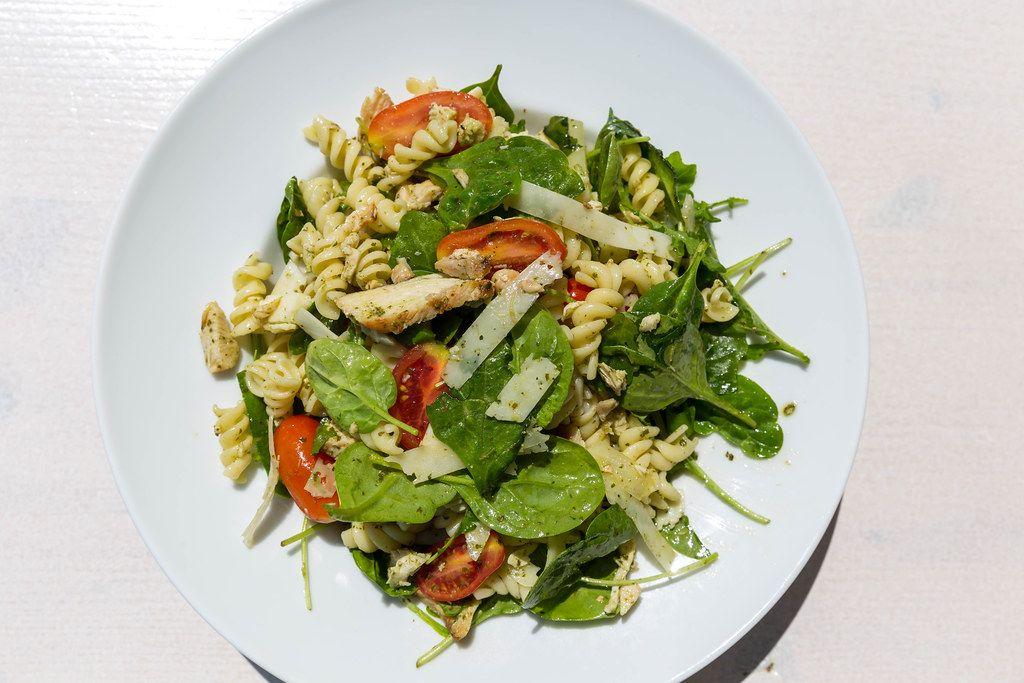 Griechisches Nudelgericht mit grünen Blättern, Tomaten und Parmesan