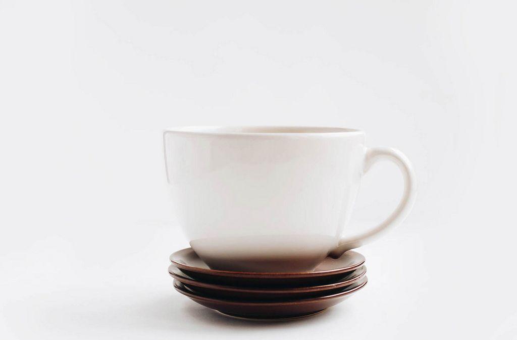 Große weiße Tasse und Nachtischteller vor weißem Hintergrund