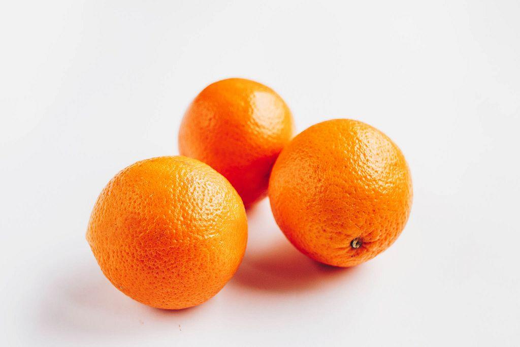 Group of three oranges on white background