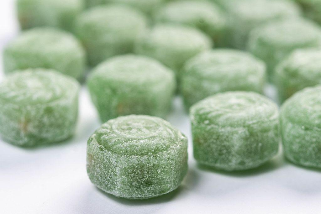 Grüne Menthol-Drops auf weißem Tisch