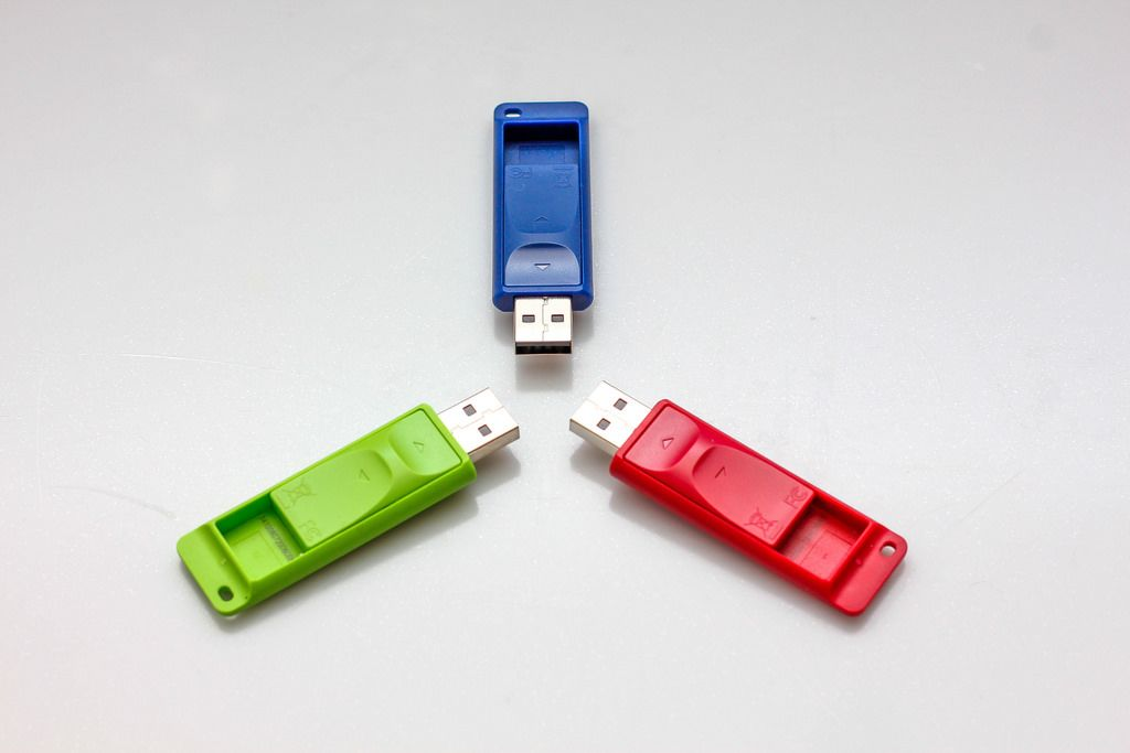 Grüner, blauer und roter USB-Speicher-Stick vor weißem Hintergrund