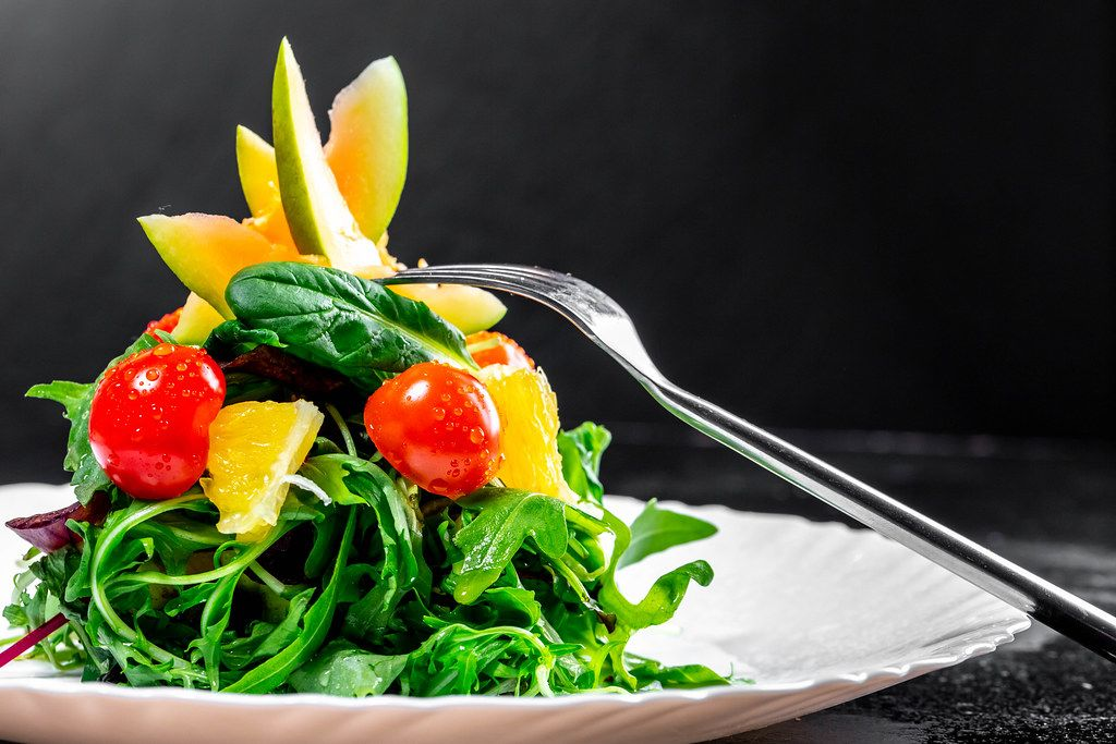 Grüner Salat mit frischen Kräutern, Cocktailtomaten, Orange und Avocado mit einer Gabel auf einem weißen Teller