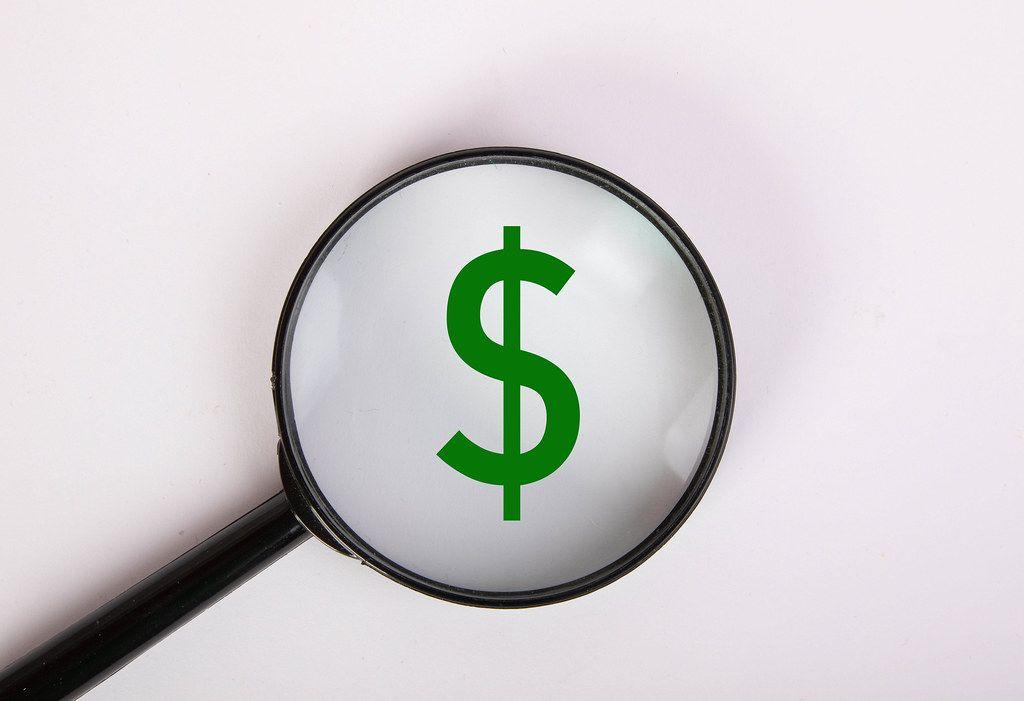 Grünes Dollar-Zeichen, vergrößert dargestellt unter einer Lupe