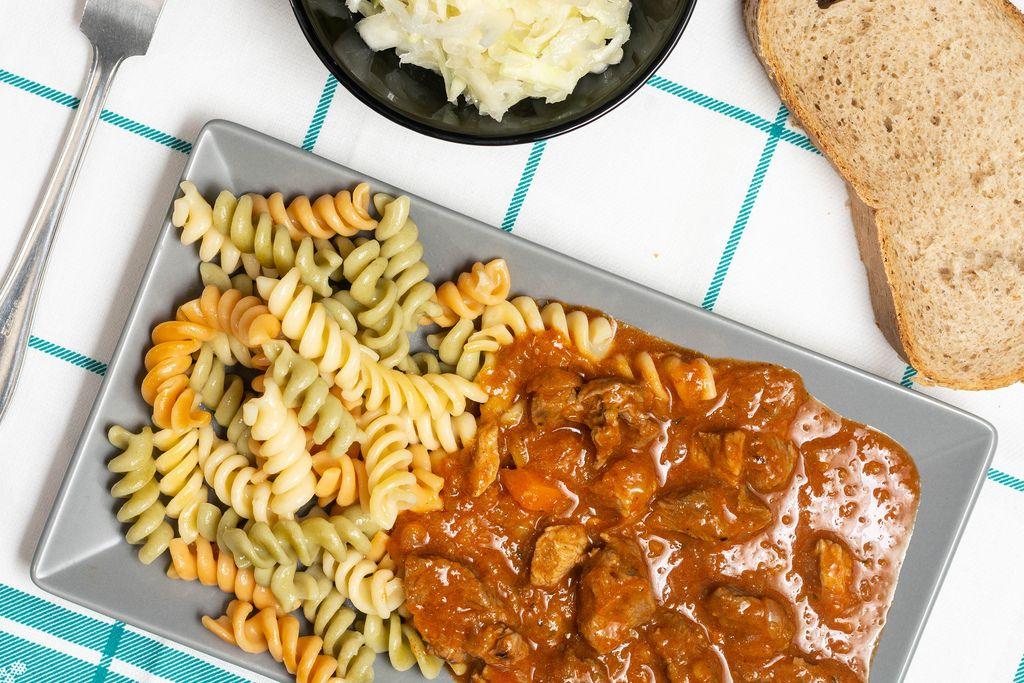 Gulasch mit Fleisch und Tomaten serviert mit Fusilli., Salat und Brotscheibe auf Tisch
