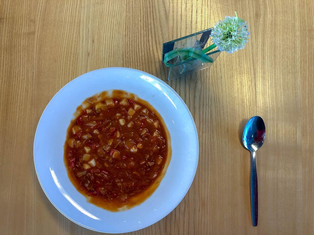 Gulasch mit Kartoffeln und Paprika in Suppenteiler mit Löffel auf Holztisch
