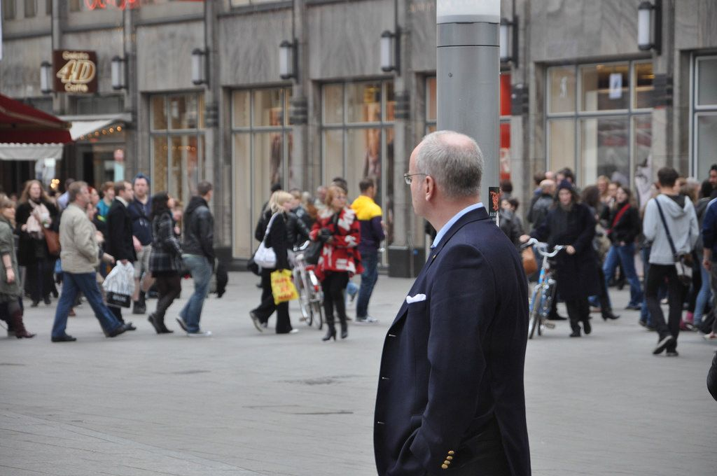 Gut gekleideter Mann beobachtet Passanten