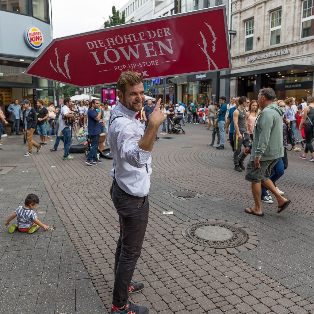 Gut gelaunter Sign Spinner in der Kölner Innenstadt