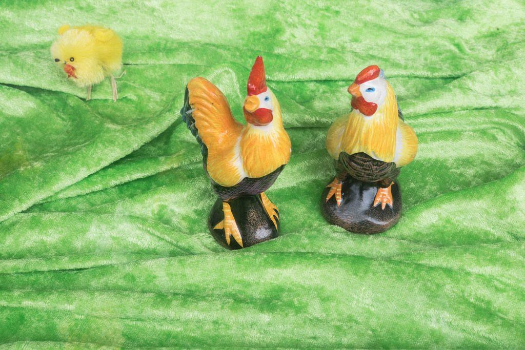 Hahn und Huhn aus Porzellan auf einem grünen Tuch