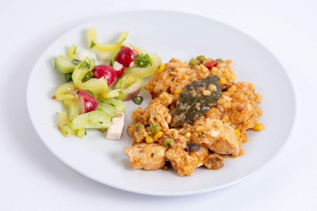 Hähnchen-Risotto mit Salat auf einem Mittagessens-Teller