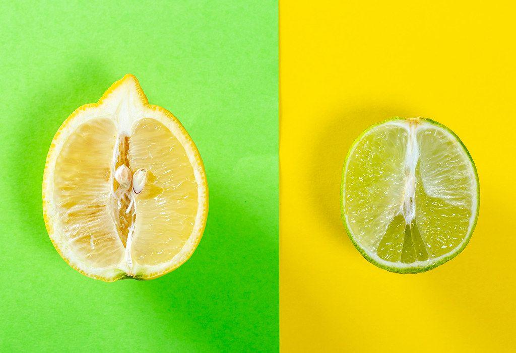Halbierte Zitrone und halbierte Limone, mit farblich passendem Hintergrund