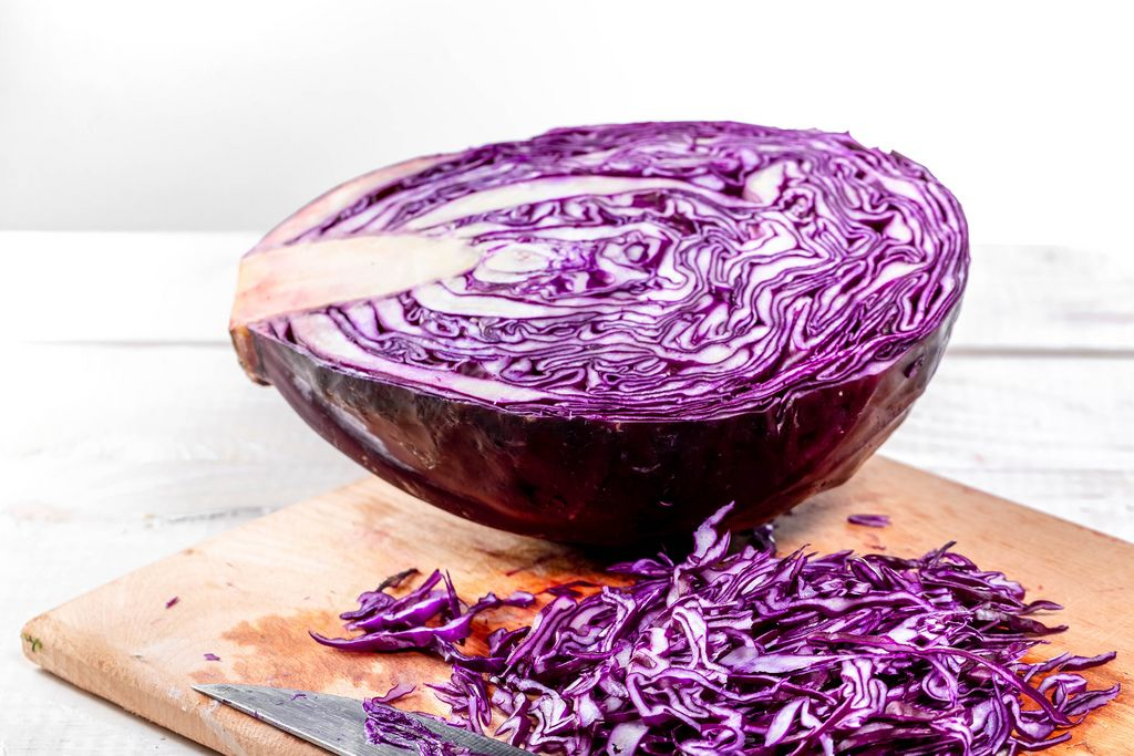 Half a red cabbage with sliced pieces on the table