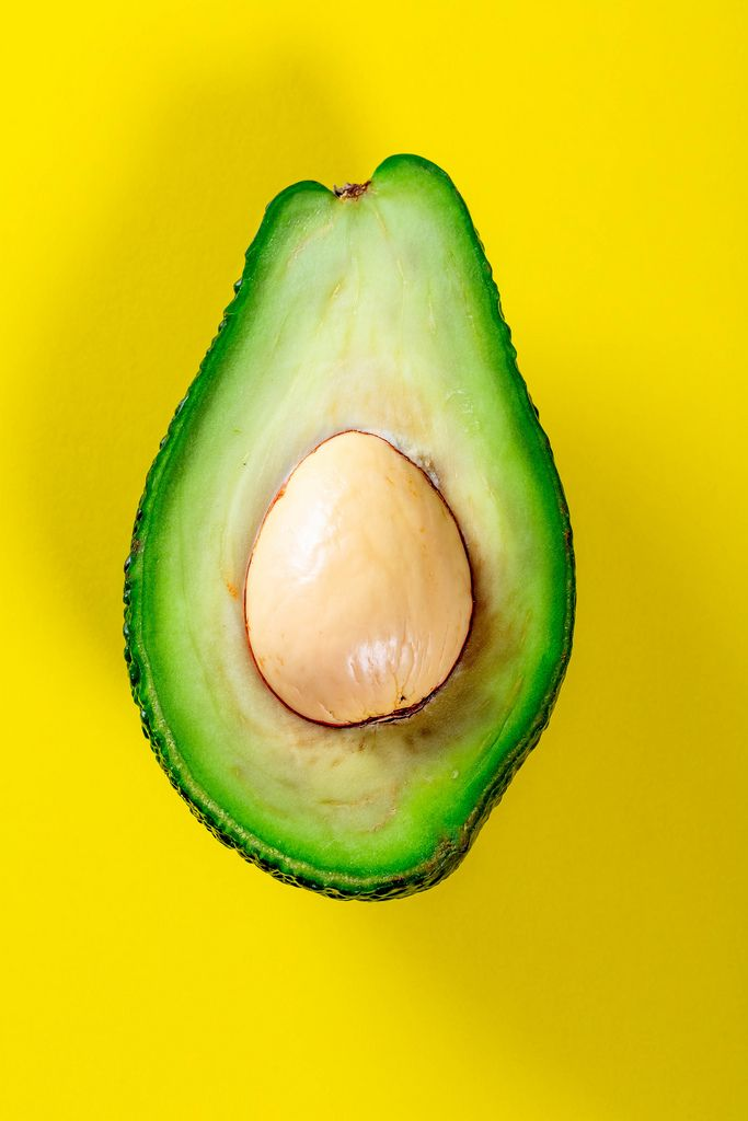Half Avocado with the pit on a yellow background