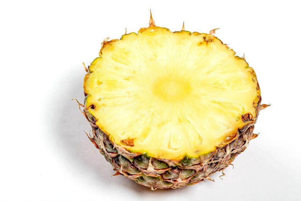 Half ripe fresh pineapple on white background