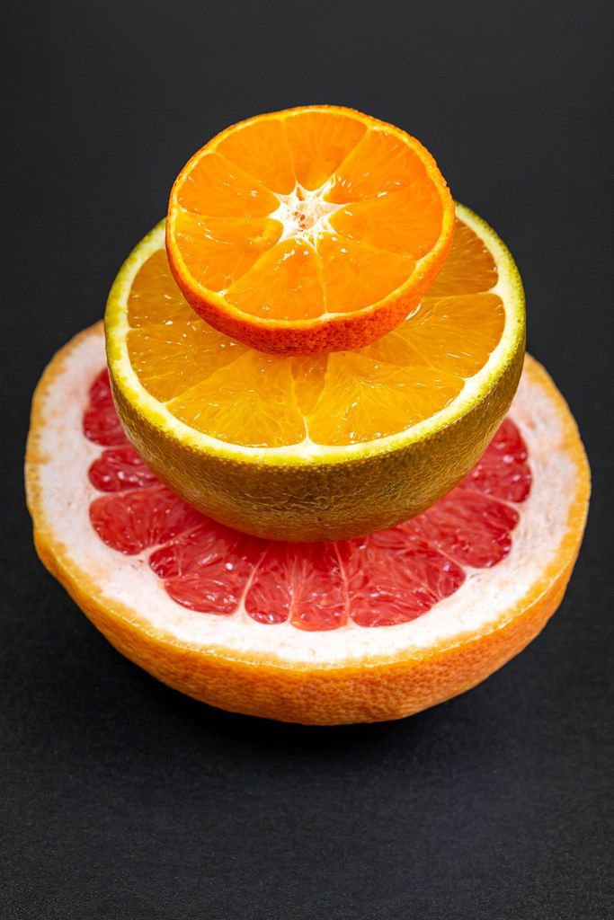 Halves of grapefruit, chocolate orange and mandarin on a black background