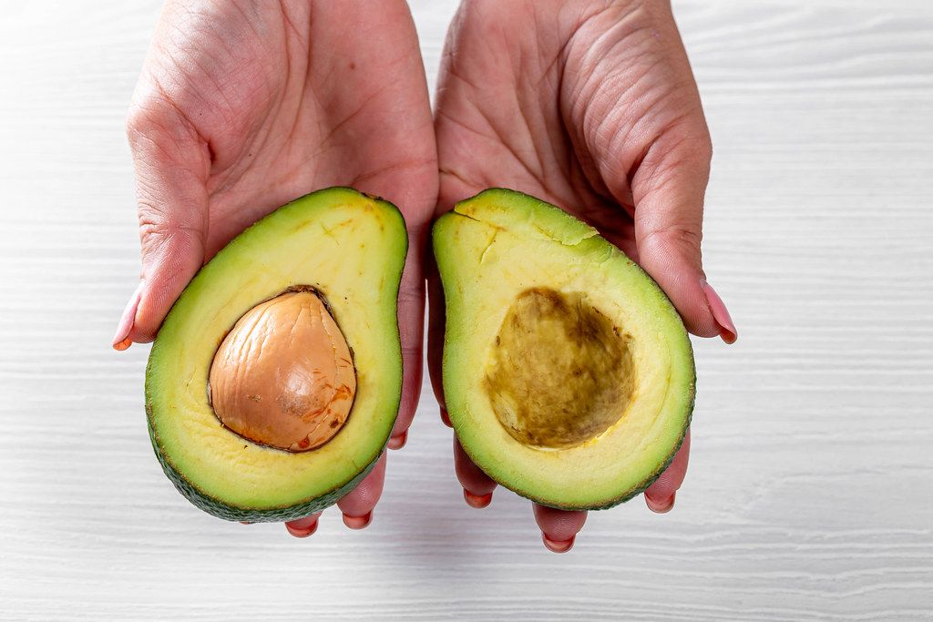 Halves of ripe avocado in the hands of a woman