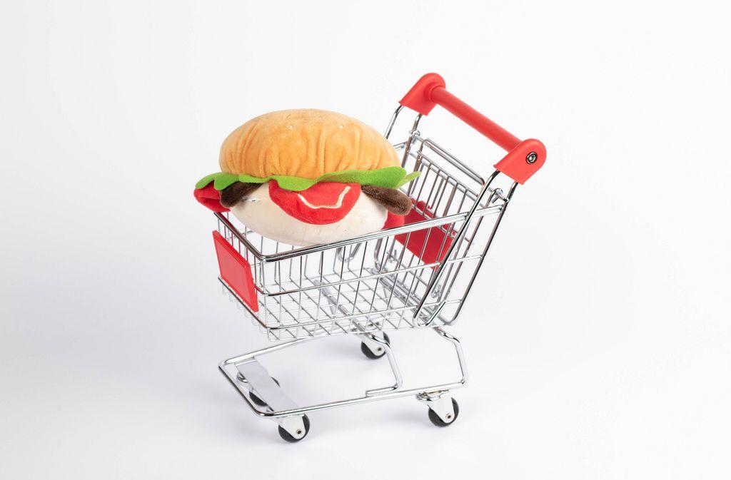 Hamburger aus Stoff in Einkaufswagen vor weißem Hintergrund