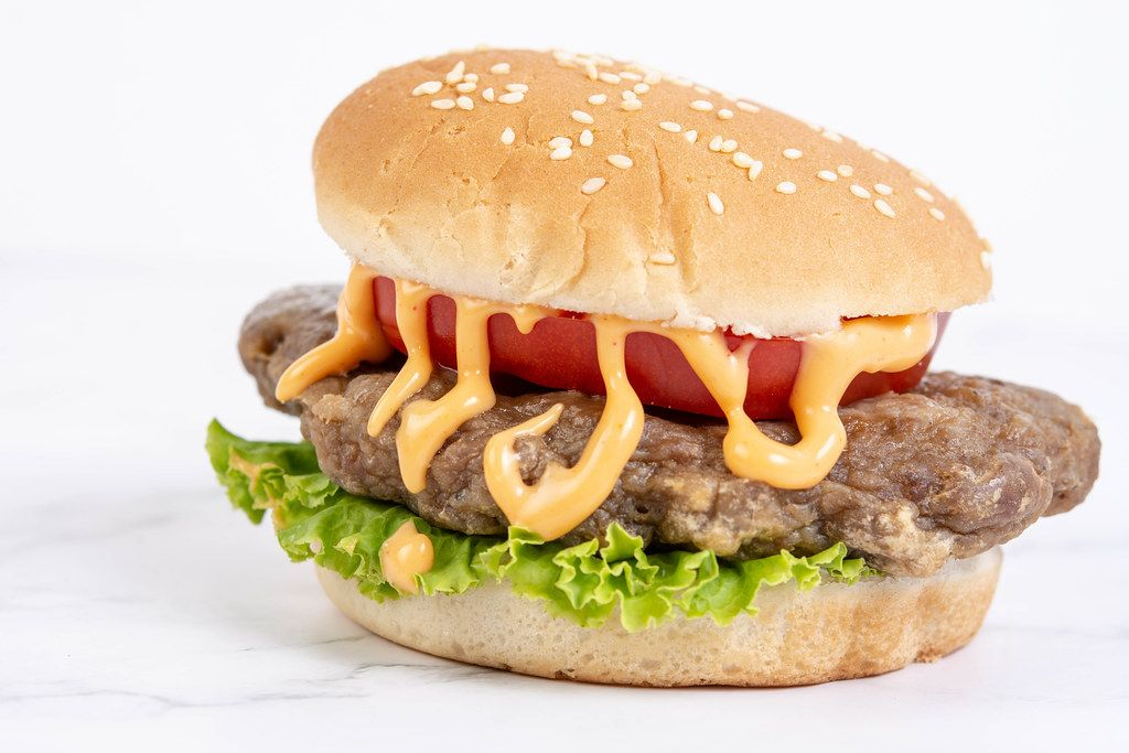 Hamburger with Tomato Lettuce and Sauce above white background