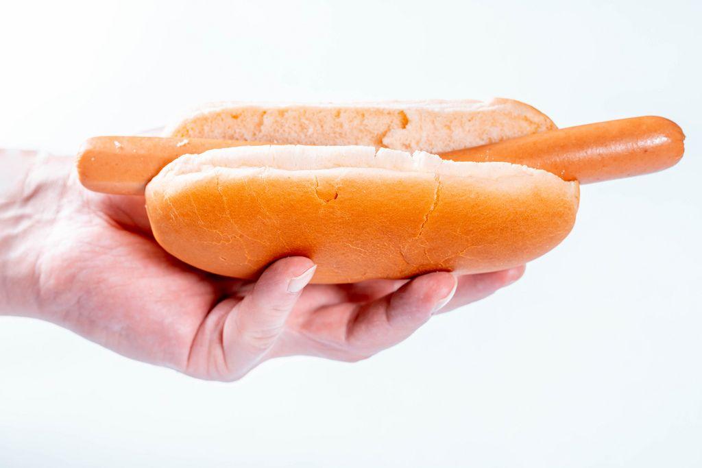 Hand eines Mannes hält Hotdog ohne Soße oder weitere Zutaten vor weißem Hintergrund