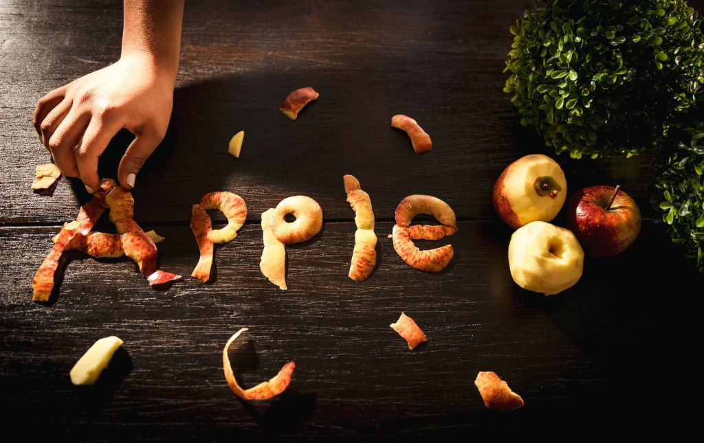 Hand forming the word APPLE with apple peel