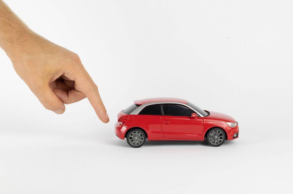 Hand gibt dem Spielzeugauto einen Schubs