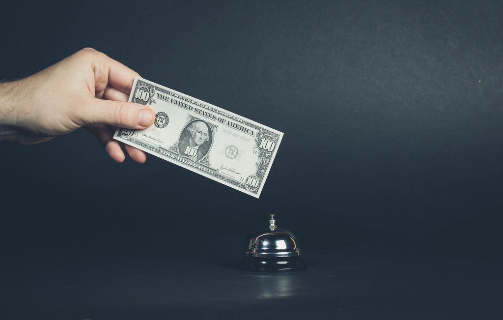 Hand hält Banknote über silberne Serviceklingel vor dunklem Hintergrund