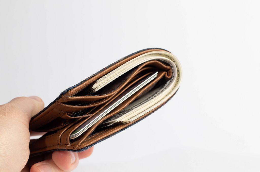 100 dollar banknoten fallen aus ge ffneter brieftasche aus. Black Bedroom Furniture Sets. Home Design Ideas