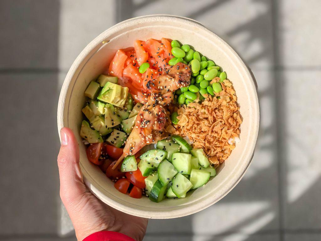Hand hält das Tagesgericht Surf and Turf Bowl von Eat Simple, mit Hähnchen, Röstzwiebeln, Favabohnen und Gemüse