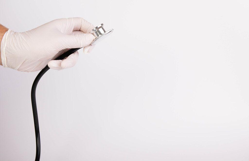 Hand hält ein Doktor-Stethoskop vor weißem Hintergrund