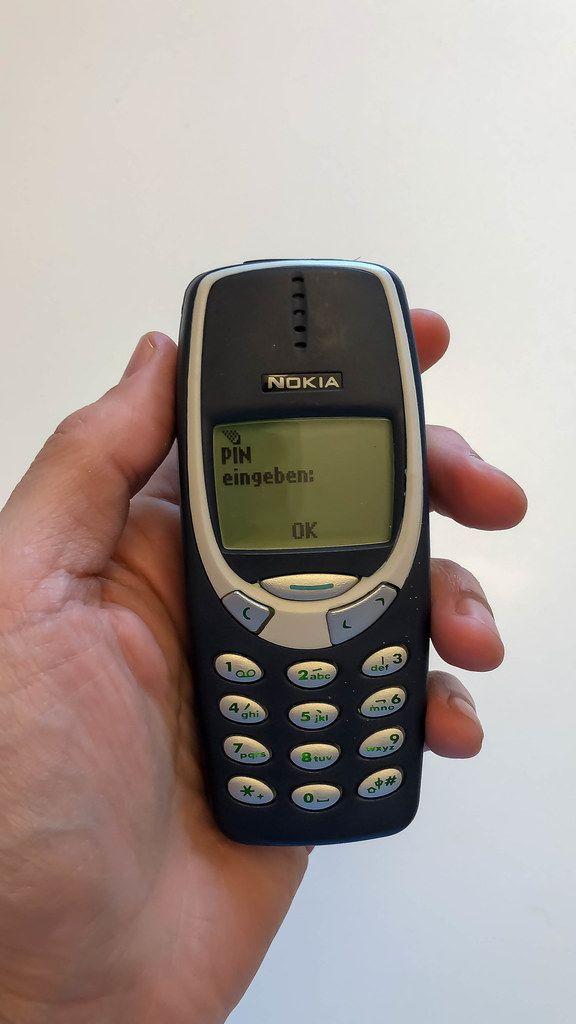 Hand hält ein klassisches Nokia 3310 Handy vor weißem Hintergrund