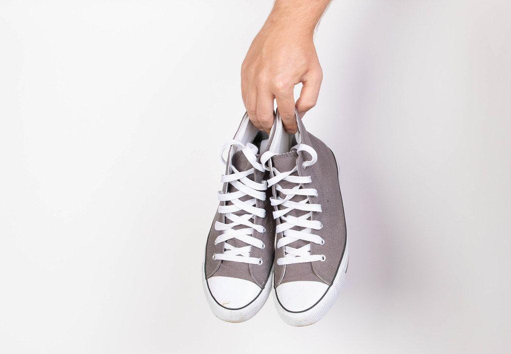 Hand hält ein Paar grau-weiße Sneaker vor weißem Hintergrund