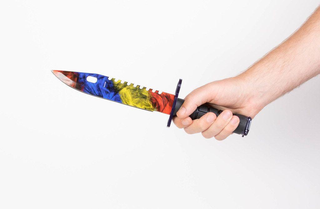 Hand hält ein Rambomesser mit bunter Klinge, vor weißem Hintergrund