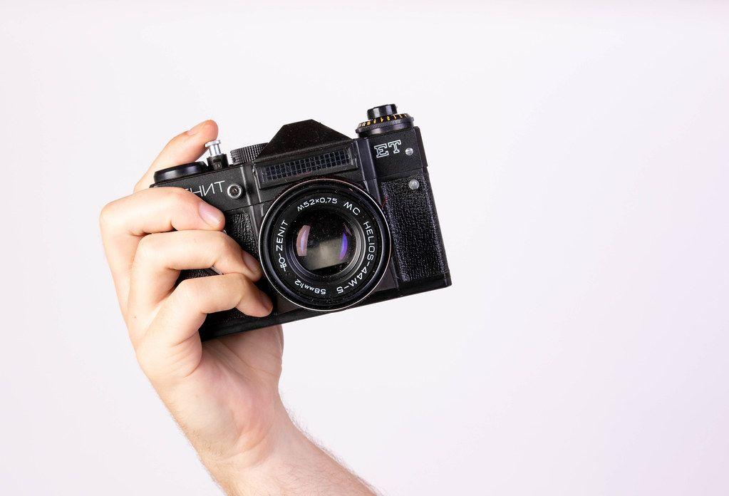 Hand hält eine alte Vintagekamera im Retrostil in die Kamera, vor weißem Hintergrund