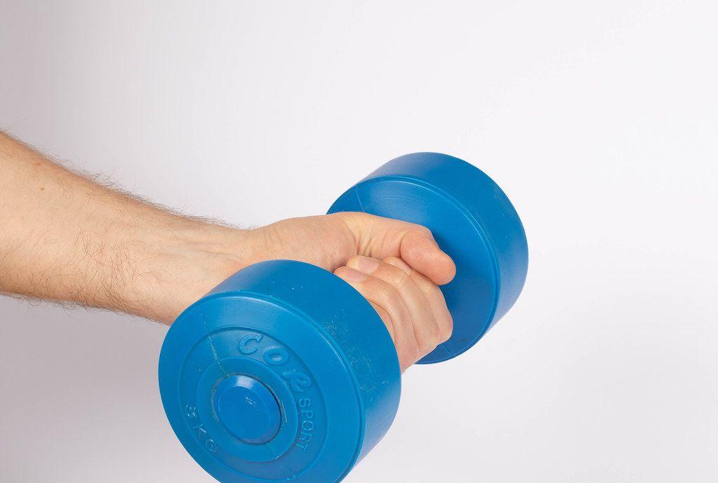 Hand hält eine blaue Hantel, vor weißem Hintergrund